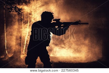 Black Silhouette Of Soldier In The Smoke Moving In Battle Operation. Back Light, Cropped, Toned And
