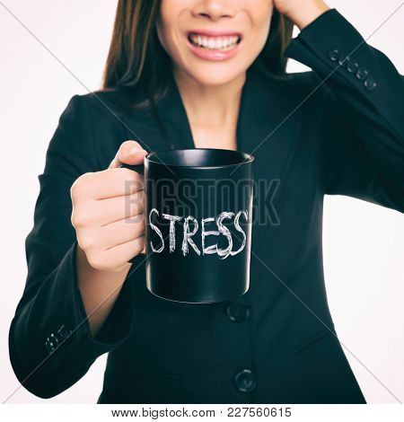 Stress - businessperson stressed at office. Business woman holding coffee cup with STRESS written. Overworked and over caffeinated female businesswoman.