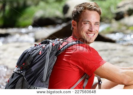 Outdoor healthy happy smiling young man hiker in his 20s with backpack hiking in forest enjoying summer vacation. Active outdoors lifestyle.