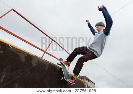 A Teenager Skateboarder In A Hat Does A Rocks Trick On A Ramp In A Skate Park Against A Cloudy Sky A