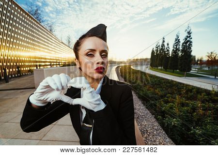 Attractive Young Woman Stewardess In Uniform Loves Her Job, Waits For Flight, Sends An Air Kiss