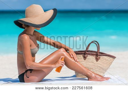 Sunscreen suntan lotion spray skincare product woman putting tanning oil on her legs. Sunblock or mosquito repellent bottle spraying on body sunbathing at beach summer vacation.