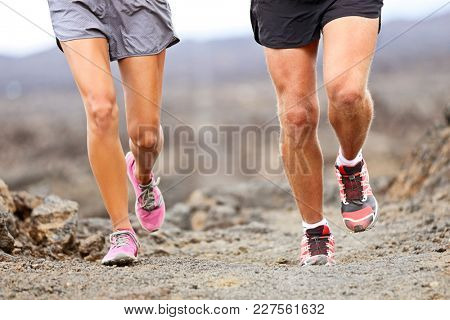 Runners running shoes on trail run. Ultra running athletes legs closeup on desert trail.