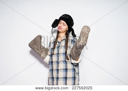 Sad Young Russian Girl In A Black Hat With Ear-flaps Holds Warm Winter Felt Boots