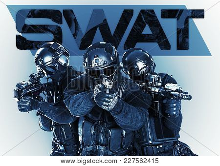 Studio Shot Of Swat Police Special Forces Black Uniforms Pointing Terrorists Automatic Rifle. Tactic