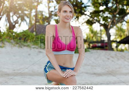 Sporty Female Athlete Dressed In Top And Shorts, Stretches On Beach, Has Warm Up Before Running Exer