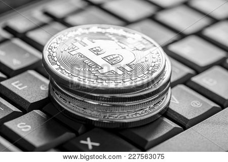 Pile Of Coins With Bitcoin Sign Over Computer Keyboard In Gresycale Image.