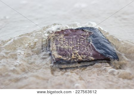 Old Leather Wallet With Drowning In Beach