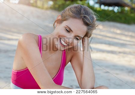 Fitness Female Athlete Runner Recreates After Cardio Training, Sits At Paceful Beach In Sunset, Has