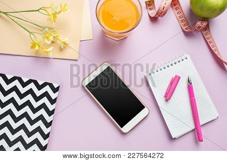 Top View Of Green Apple, Juice, Measuring Tape, Mobile Phone, Pen And Notebook On Trendy Color Pink