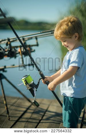 Child Smile With Fishing Rod On Wooden Pier. Little Boy Learn To Catch Fish In Lake Or River. Summer
