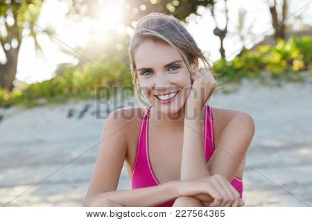Happy Woman Gets Ready For Race, Sits Against Sunrise At Sandy Beach, Has Healthy Lifestyle, Positiv