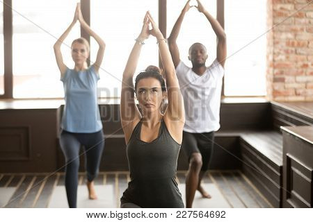 Group Of Young Sporty People Practicing Yoga Lesson With Instructor, Standing In Warrior One Exercis