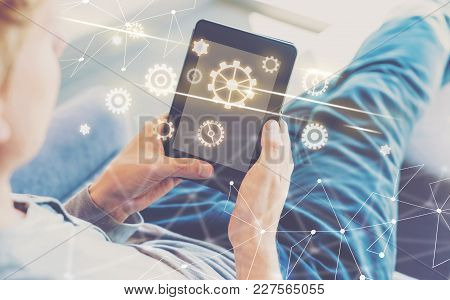 Gears With Man Using A Tablet In A Chair