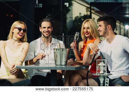 Happy Friends Vapor Hookah And Drink Alcohol In Bar Lounge. Twins Women And Men Relax In Shisha Cafe