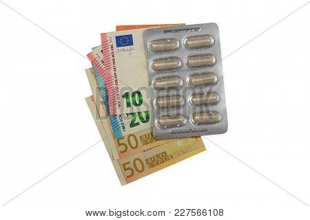 Package of herbal medicine in clear capsules on Euro banknote money isolated on white