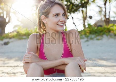 Fitness Woman In Top Looks Away With Happy Expression, Enjoys Good Rest Outdoor, Involved In Sport S