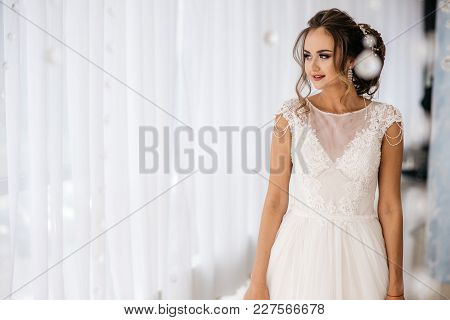 Beautiful Bride In White Wedding Dress Is Standing In Boudoir Room And Smiling. Place For Text