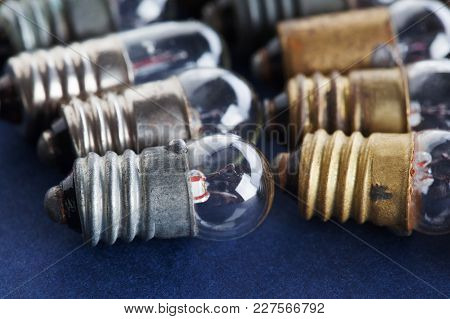 Light Bulbs Set On Blue Paper Background. Colorful Gold Bronze And Silver Vintage Lamps. Macro View