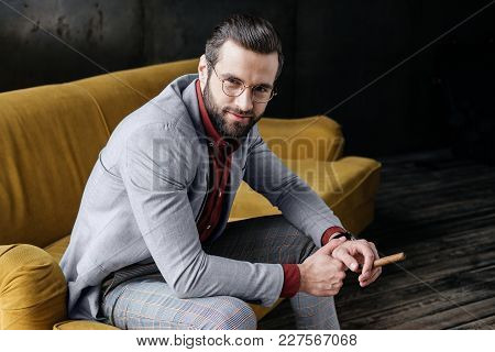 Fashionable Bearded Man With Cigar Sitting On Couch