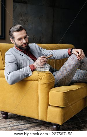 Stylish Handsome Man With Cigar And Ashtray Sitting On Couch