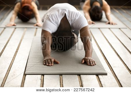 Young Black Man And Group Of Young Sporty People Practicing Yoga Lesson With Instructor, Stretching