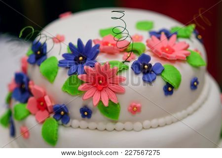 Wedding Cake In White Sweet Glaze With Multicolored Flowers Close Up