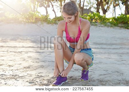 Glad Sporty Girl Laces Purple Sneakers During Running Exercise Outdoor At Beach Against Sunshine. Ha