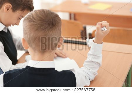 Little boy making paper ball in classroom