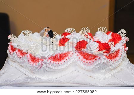 White Cream Wedding Cake Decorated With Red Roses With Bride And Groom Figurines