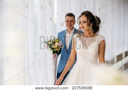 Meeting The Bride And Groom In The Boudoir Room. Man Behind Woman With Flowers In Hands