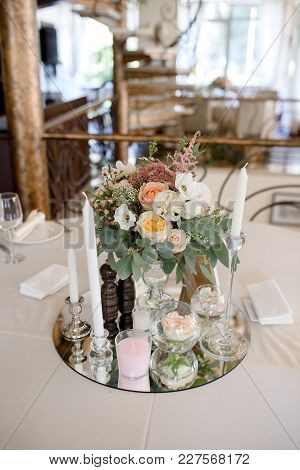 Decorated Table With Flowers And Candles On The Mirror Plate