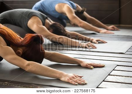 Group Of Young Sporty Afro American And Caucasian People Practicing Yoga Lesson Stretching In Child