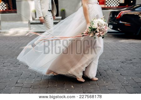 Bride's Hands With Wedding Bouquet With Roses And Long Pink Ribbons