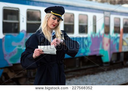 The Blond Hair Female Railroad Employee Or Railway Worker Is Checking Time On Her Watch And Holding