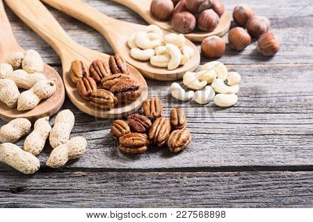 Mix Of Nuts In Wooden Spoon . Pecan , Hazelnut , Pistachios , Cashew And Peanuts