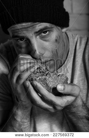 Hungry poor man eating piece of bread