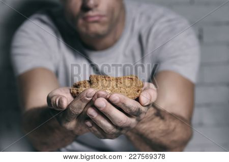 Homeless poor man with piece of bread, closeup