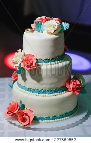 Wedding Cake With Tiers In White Glaze Decorated With Cream Flowers On The Table