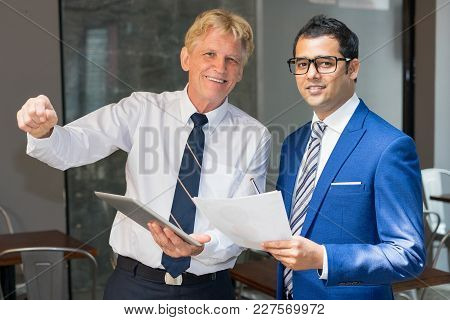 Two Happy Men In Ties With Tablet, Documents And Pen At Office Cafe. Business Partners Meeting For S