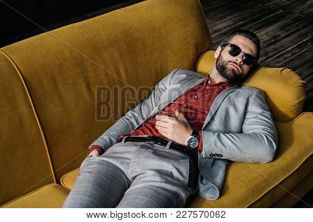 Stylish Drunk Man In Sunglasses With Glass Of Cognac Lying On Yellow Sofa