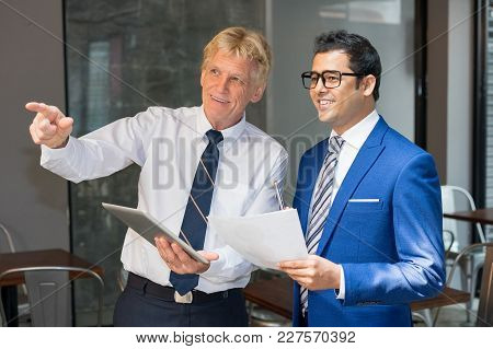 Senior Businessman Pointing Finger And Showing Something To Junior Partner At Office Cafe. Business