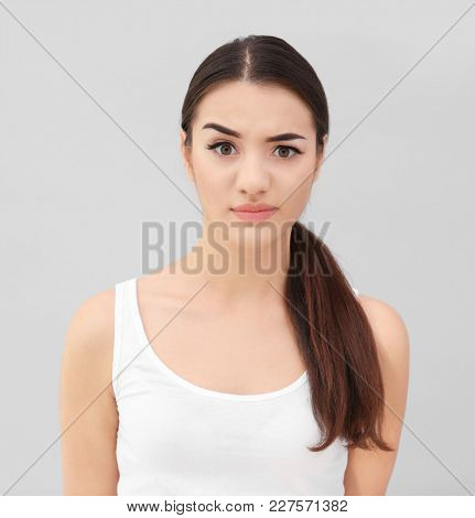 Emotional young woman with beautiful eyebrows on light background