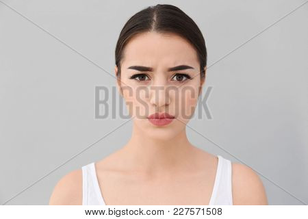 Young woman frowning her eyebrows on light background