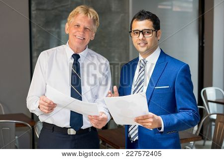 Indian And Caucasian Businessmen Holding Documents And Smiling At Camera. Top Managers Reviewing Con