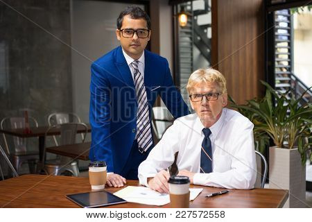 Young And Senior Businessmen Drinking Coffee And Discussing Project. Two Business Partners Analyzing