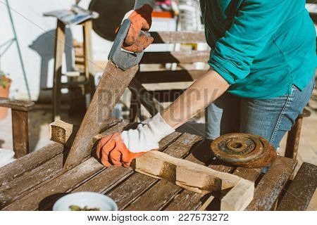 Woman Sawing A Wood, With Work Gloves On The Table In The Terrace. Of Day