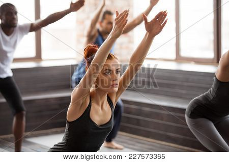 Group Of Young Afro American And Caucasian Sporty People Practicing Yoga Lesson Standing In Chair Ex