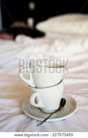 two white ceramic empty cups of coffee on the white sheets of an unmade bed