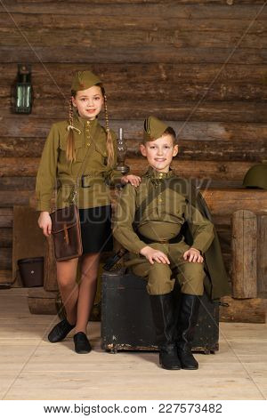 Couple children in the old-fashioned Soviet military uniform with a binoculars on the background of a dugout from the bars